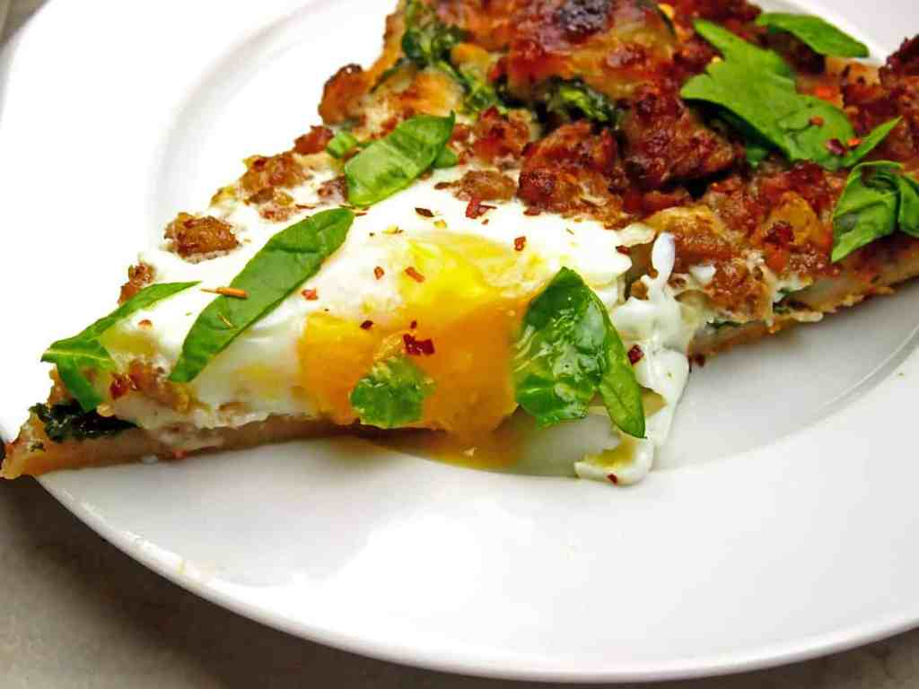Close up of pizza slice with drippy egg, breakfast sausage, and spinach on top.