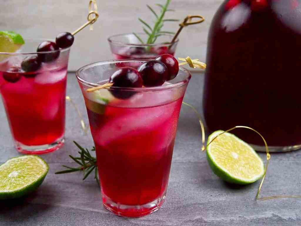 Glass of cranberry margarita garnished with rosemary, lime, and fresh cranberries