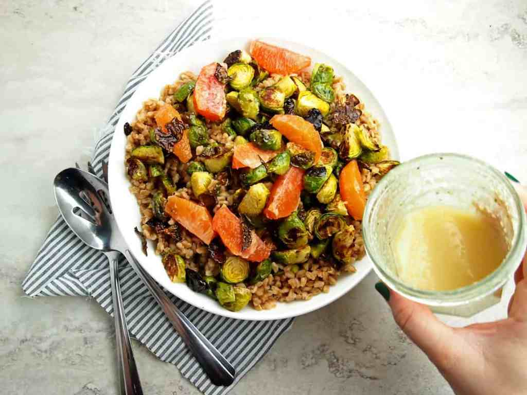 Drizzling of citrus vinaigrette on farro salad with brussels sprouts