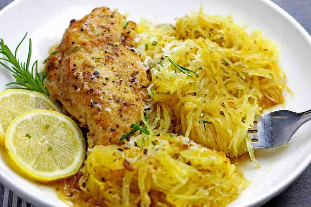 A plate of braised lemon chicken with spaghetti squash with a fork