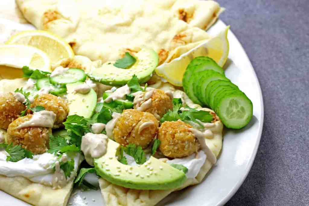 Sesame falafel with avocado, sesame seeds, and cucumber slices on a serving platter