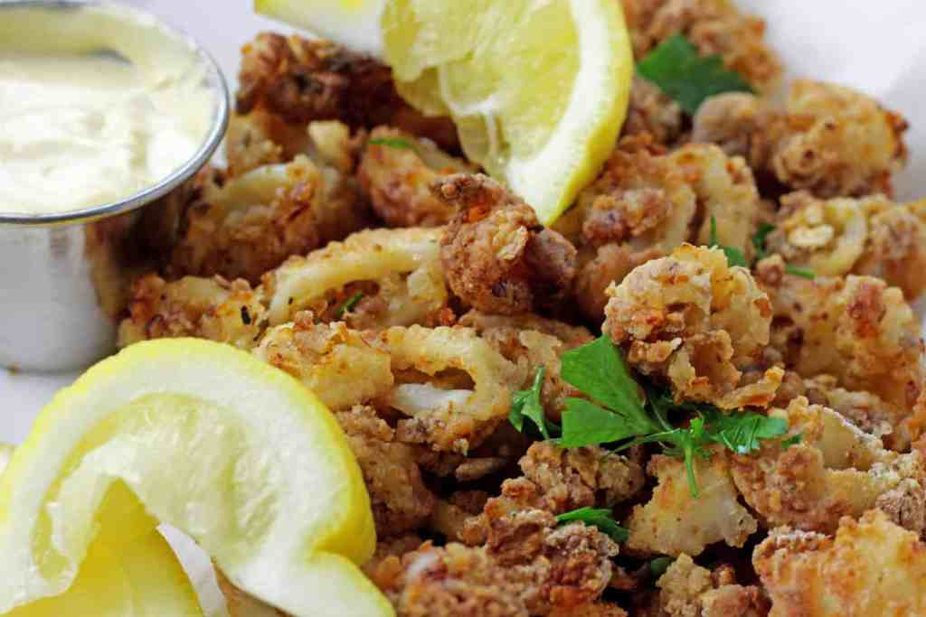 Close up of crunchy air fryer calamari with lemons, parsley, and mustard dipping sauce