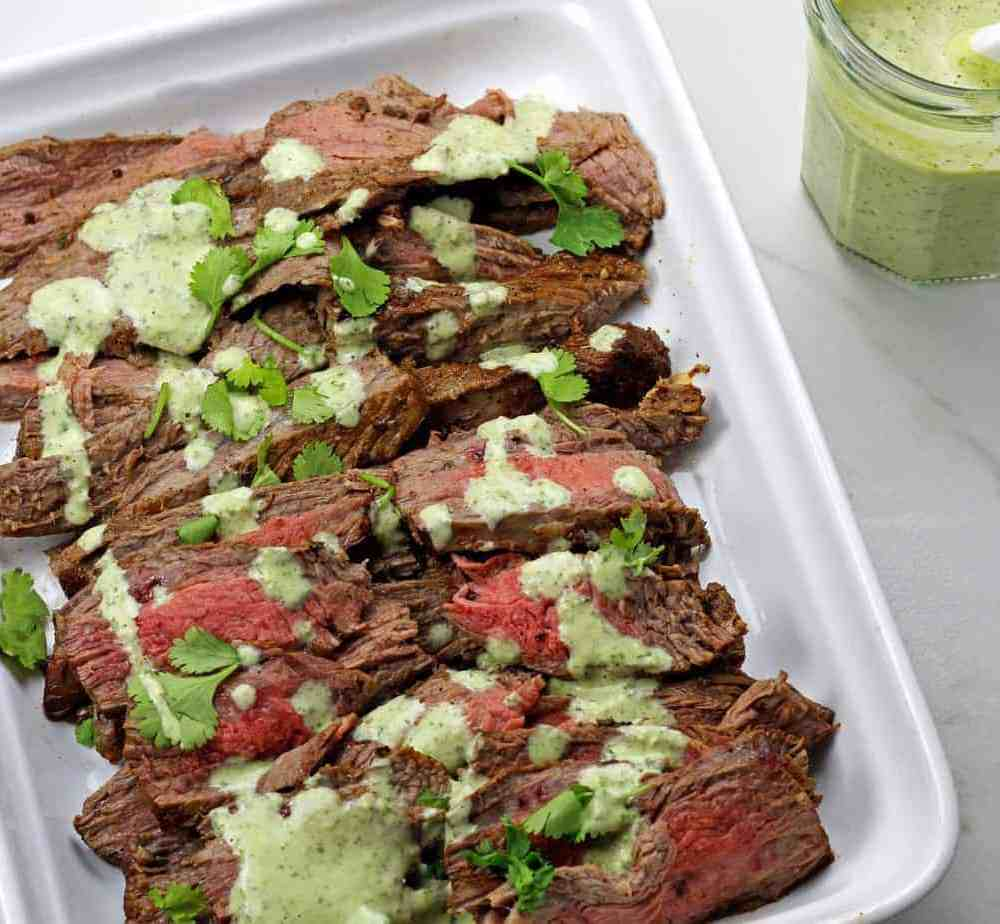 Platter of instant pot carne asada with cilantro garlic sauce drizzled on top and a jar of the sauce on the side.