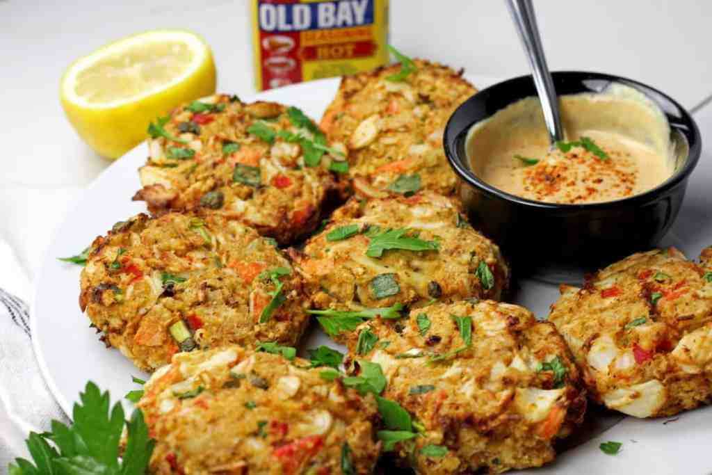Close up of air fryer crab cakes with a sauce with Old Bay Seasoning in the background