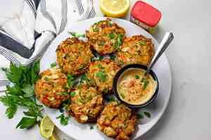 Overview of air fryer crab cakes with a sauce on a white background