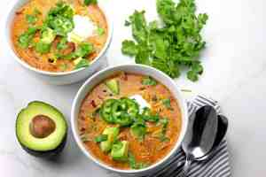 Overview of two bowls of creamy enchilada soup with a spoon in the bowl on a white countertop
