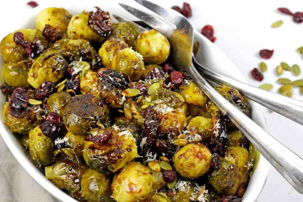 Close up of smashed brussels sprouts in a bowl with pepitas, cranberries and balsamic glaze with serving spoons.