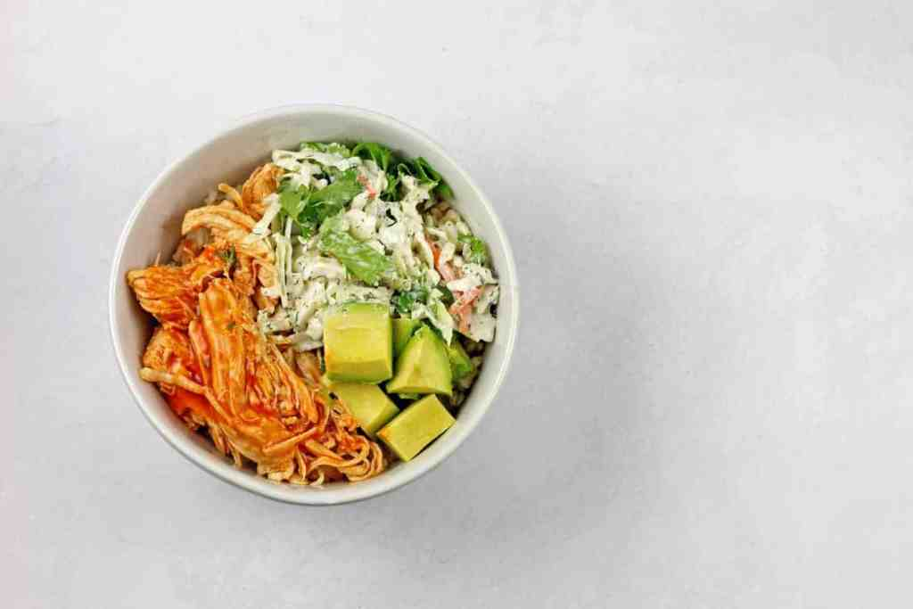 Overhead view of the buffalo chicken rice bowl on a white background.