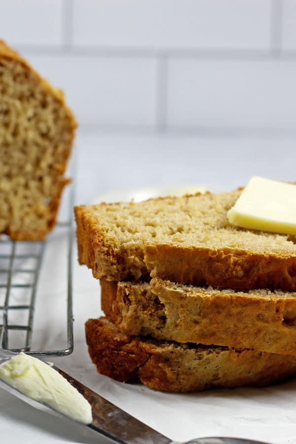 3 slices of 3 ingredient beer bread stacked with pat of butter on top on a white background with the loaf of beer bread in the background and a butter knife in the foreground