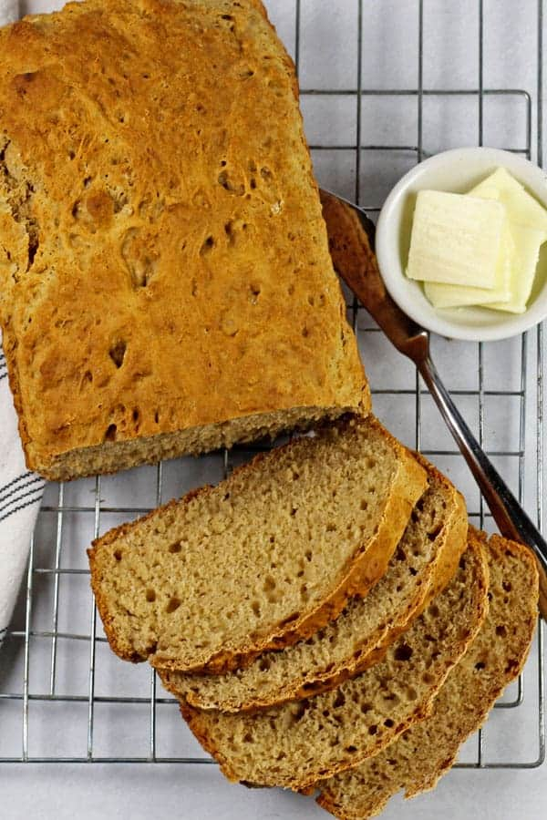 A loaf of 3 ingredient bread sliced on a cooling rack with a blue and white napkin, butter knife, and a little bowl of butter on the side on a white background