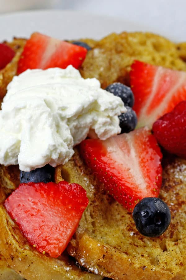 Close up of sourdough french toast with strawberries, blueberries, and yogurt on top on a white plate.