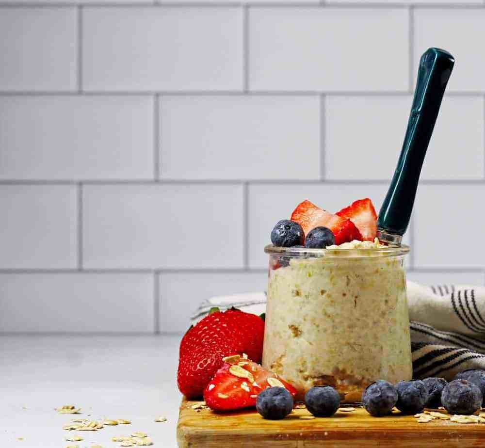 A jar of vanilla overnight oats with fruit and a spoon on a wooden cutter board and a white and blue napkin along with white subway tile in the background.