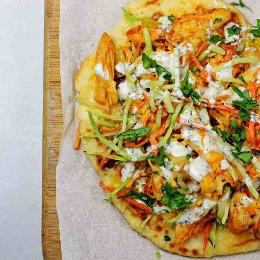A buffalo chicken flatbread sitting on top of a parchment paper lined cutting board on a white counter.