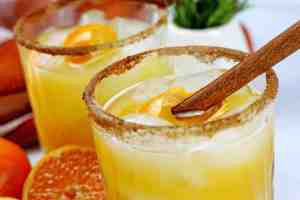 An close up of the pumpkin spice margarita that has a orange peel and whole cinnamon stick on top. The margaritas have a cinnamon sugar rim. There are whole cinnamon sticks, slice oranges, and orange kitchen towel, and springs of rosemary in a white cup.