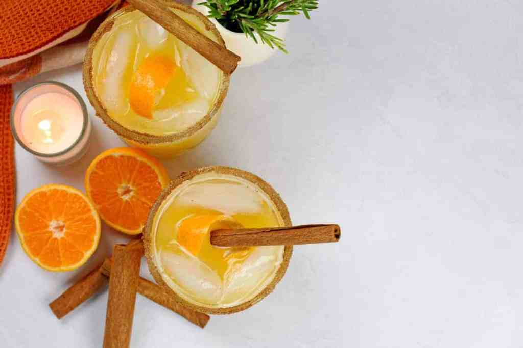 An overview of the pumpkin spice margaritas in two glasses with a cinnamon sugar rim. There are whole cinnamon sticks, slice oranges, and orange kitchen towel, and springs of rosemary in a white cup - all on a gray background.