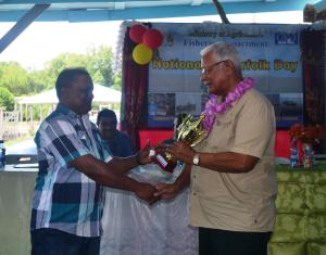 Minister Holder handing over a trophy to the olders serving fisherman persent at the Fisherfolk day celebrations