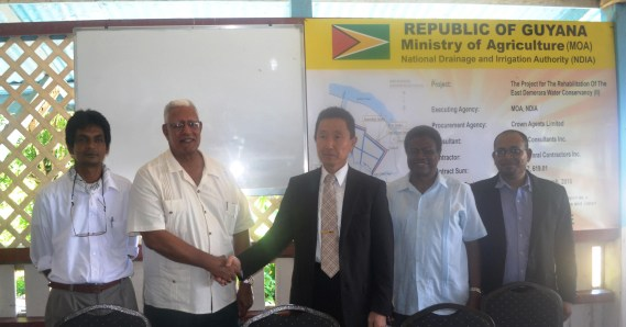 Agriculture Minister Noel Holder shakes hands with Japanese Ambassador H.E. Mitsuhiko Okada during a handing over ceremony of the Rehabilitation of the EDWC II. Theyare accompanied by other NDIA reps