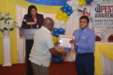 chairman-of-the-ptccb-dr-leslie-munroe-presents-a-certificate-to-a-graduate-at-the-ptccb-graduation-ceremony-as-registrar-of-the-ptccb-trecia-garnath-in-background-looks-on