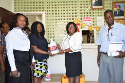 Minister of Public Health, Dr. Karen Cummings (Second from right) hands over cleaning supplies to Regional Democratic Council (RDC) Chairman, Genevieve Allen in the presence of Director of Regional Health Services, Dr. Kay Shako and Neighbourhood Democratic Council Chairman (NDC), Deon Abrams.