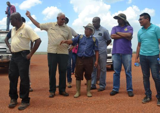 Minister Holder along with Nappi Village Toshao Walter Horatio along with other MOA representatives at one of the water catchment areas.