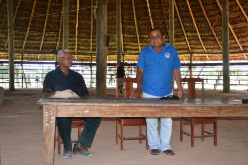 Minister Holder with the toshao of Annai Village, Mark Francis George during a meeting with villagers