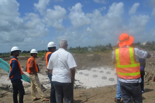 Minister Holder and engineers from Innovative Engineering Consultancy Services during a site visit to the sluice being constructed at Triumph, ECD.