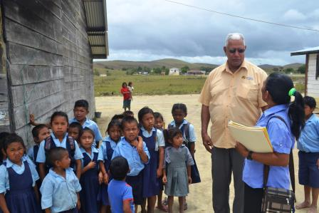 Minister Holder is pictured with students as he engages in dialogue with the Head Teacher of the Kamana Village Primary School.