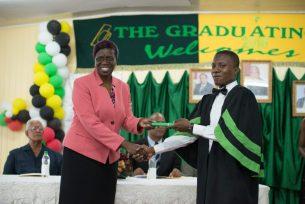 Osbert Carmichael receives a Certificate of Higher Credit from Permanent Secretary, Delma Nedd
