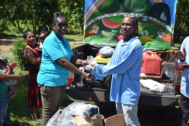 Minister within the Ministry of Agriculture, with responsibility for Rural Affairs, Hon. Valerie Adams-Yearwood handing over the items to Chairman of the Cooperative Society, Ben Smith.