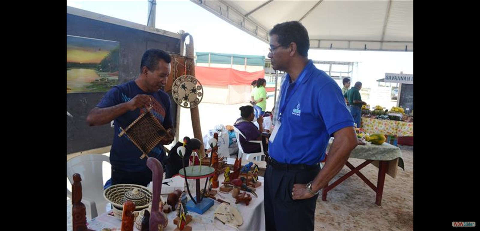 Exhibitor shows one of his items to a visitor at the Rupununi Expo