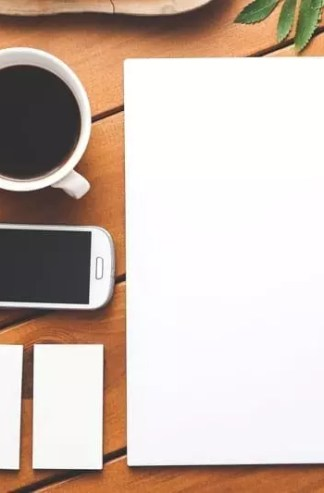 blank business cards and paper next to a pen, a phone, and a cup of coffee on a wooden table