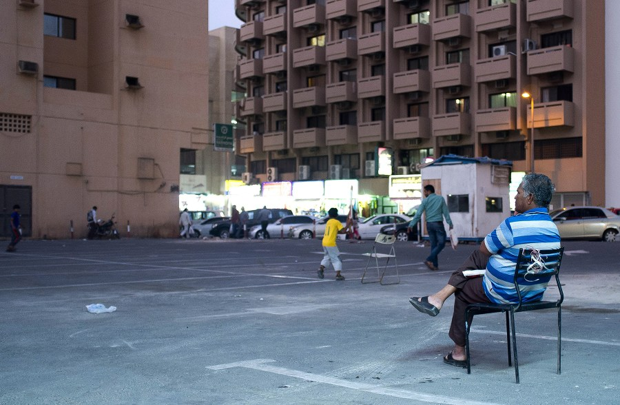 A man watches a game of cricket in a parking lot in Dubai