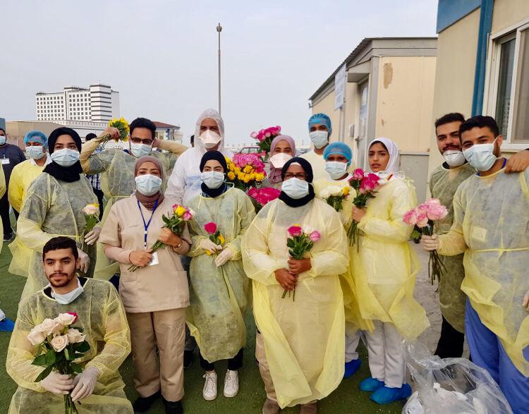 Bahraini volunteers from al-Khaldia Youth Society and others give flowers to people at al-Hidd quarantine site (Photo by Bahraini Member of Parliament Jalal Kazem)