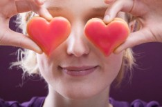 Young woman with two heart-shaped biscuits in front of her eyes
