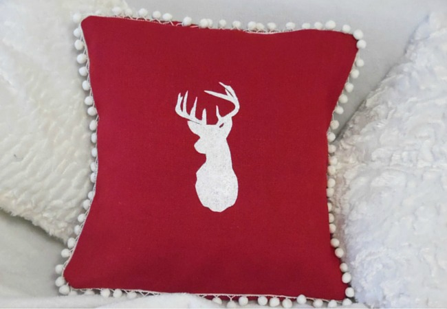 Red Burlap Cushion With Pom Pom Trim And Deer Head Motif