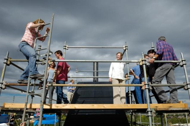 Staff members make their way up the ladder to stand on the scaffold surrounding the very top of the cone.