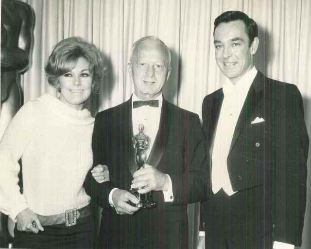 Kim Novak, Ernest Laszlo, and Richard Johnson at the Oscars.  E