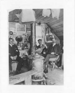 Photo of 3 men sitting inside the Woodrock Ranger Station in Wyoming. One of the men is playing a stringed instrument.
