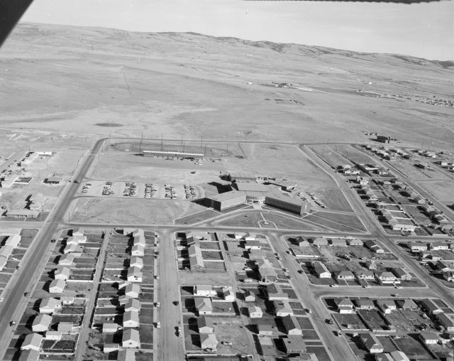 Black and white photo looking east towards the Laramie Mountains. Houses are visible on all sides of the former Laramie High School, except for east. East of the former high school is an empty field with the Laramie Mountains in the background.