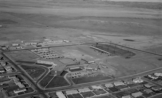 Black and white photo of Laramie High School and Deti Stadium looking northeast toward W Hill, there is a W visible on the hill. Houses are visible on the south and west sides of the former Laramie High School, while there are empty fields to the north and east sides.