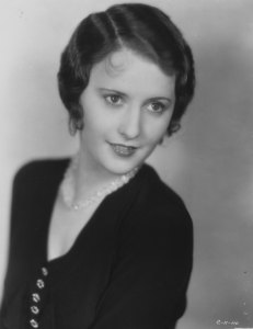 Black and white portrait photo of Barbara Stanwyck wearing a black sweater.