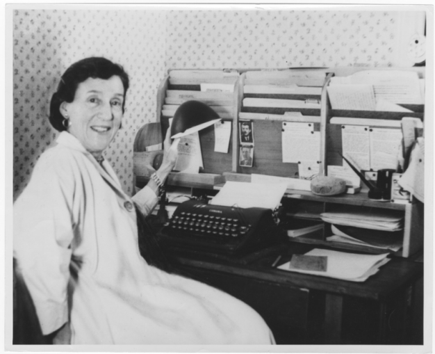 woman sitting at desk with typewriter, file folders, and paperes.