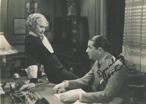 woman sitting at a desk staring at a man in a suit.