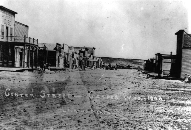 black and white image; dirt road in center of a town -- featuring many wooden buildings