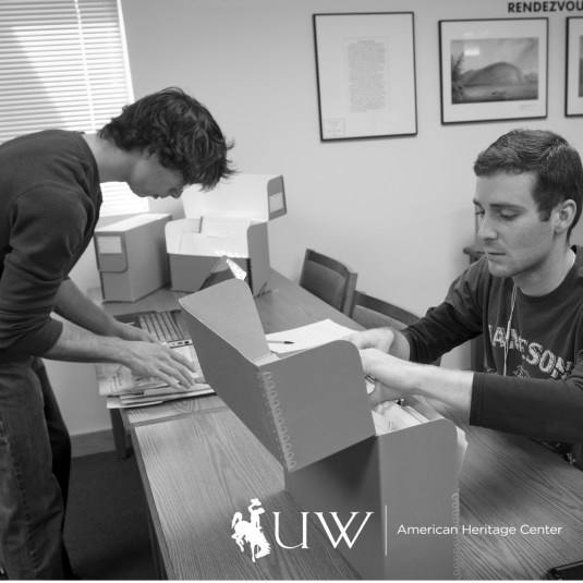 black and white image of two people around a table using archives and doing research. AHC logo