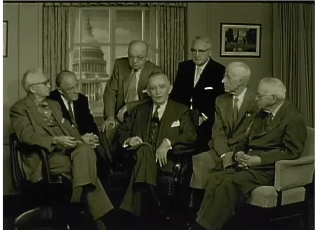 men in suits sitting in chairs inside a room