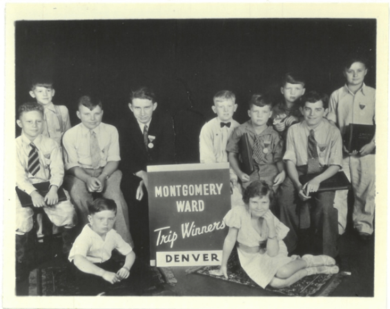 group of kids sitting and standing posing for a photo with a banner