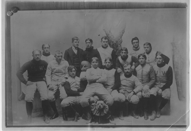 black and white photo of group of men -- a football team.