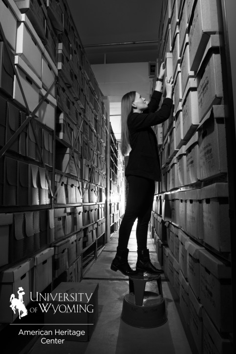 person standing on stool in archive area pulling a box down
