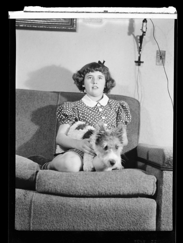 a girl sitting on a couch with her puppy dog